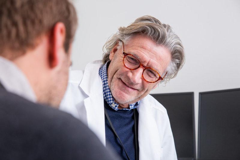 Mann med briller og hvit frakk snakker med pasient. Foto